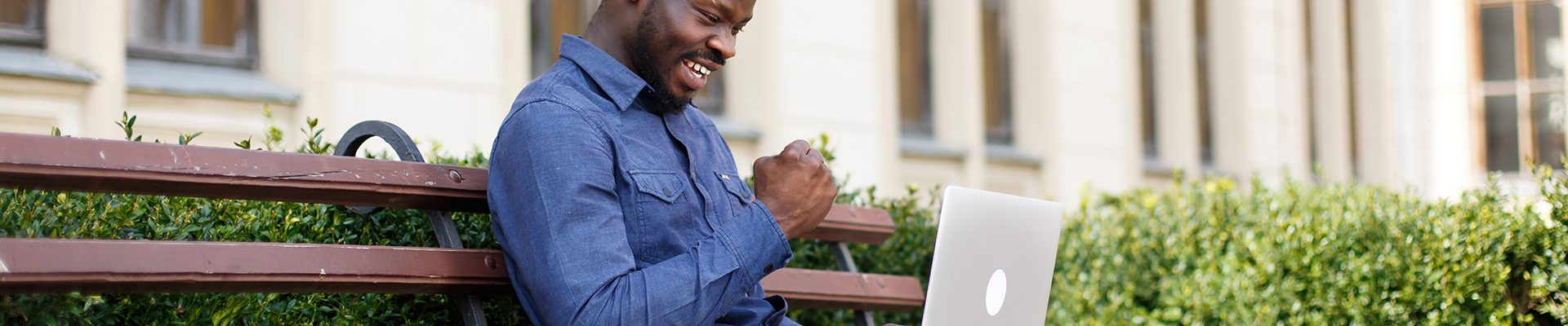 Happy African American man works on his laptop sitting on the bench outside